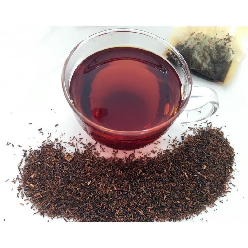 Loser Rotbuschtee - Rooibushtee rund um eine Teetasse verteilt in Hintergrund ein Papierfilter