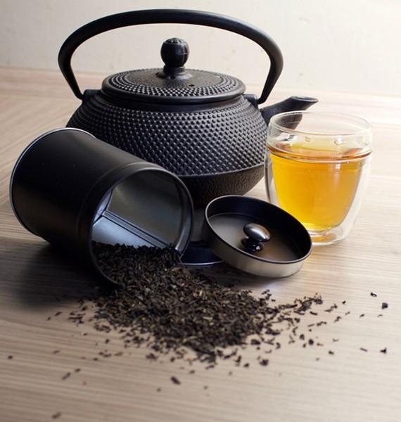 Teedose mit Teekanne und gefüllter Tasse Tee