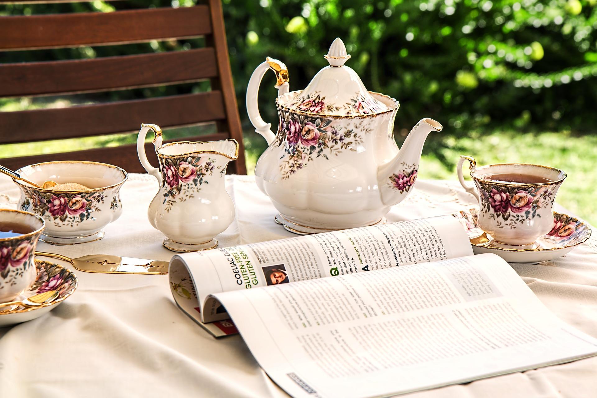 Bild mit Teekanne, Teetasse und Milchkännchen und Zuckerdose auf Gartentisch