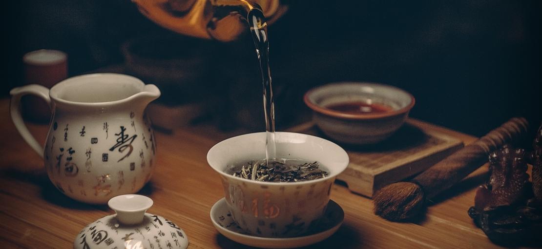 Ein Teetasse mit Tee wird gerade aufgegossen